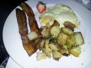 two eggs over medium with smoked bacon, chive potatoes and toast
