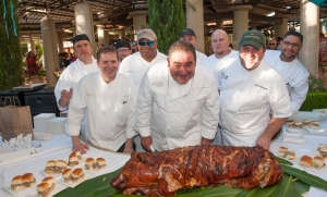 Emeril Lagasse with his team and their slow-roasted pig. (Photo Credit: Tom Donoghue)